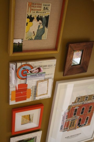 A square recycled paper bulletin board tucked in amongst the frames.