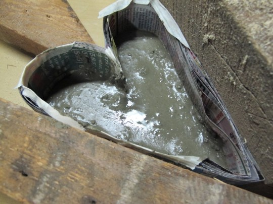 Portland cement mixed thick, being poured and scooped into the mold. Beginning to settle.
