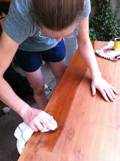 Applying stain in long, even, rag-soaked strokes.