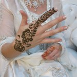 Additional henna being applied to the bride at the wedding.