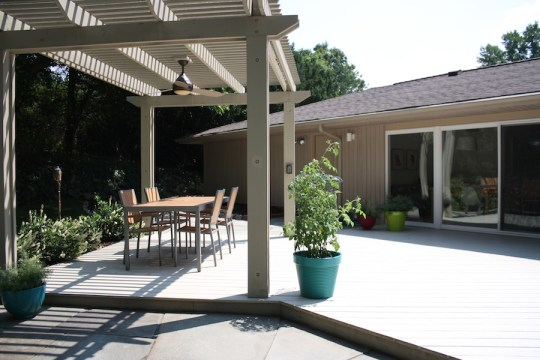 New backyard accented with a huge deck, flagstone patio, and a pergola over their outdoor eating area.