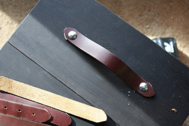 Attaching the belts to the drawers with carriage bolts.