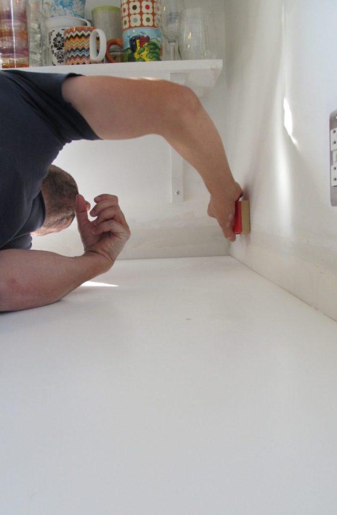 Hand sanding the walls.