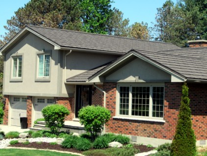 This side-split home features a weathered wood-style steel shake roof from Metal Roof Outlet in Ontario.