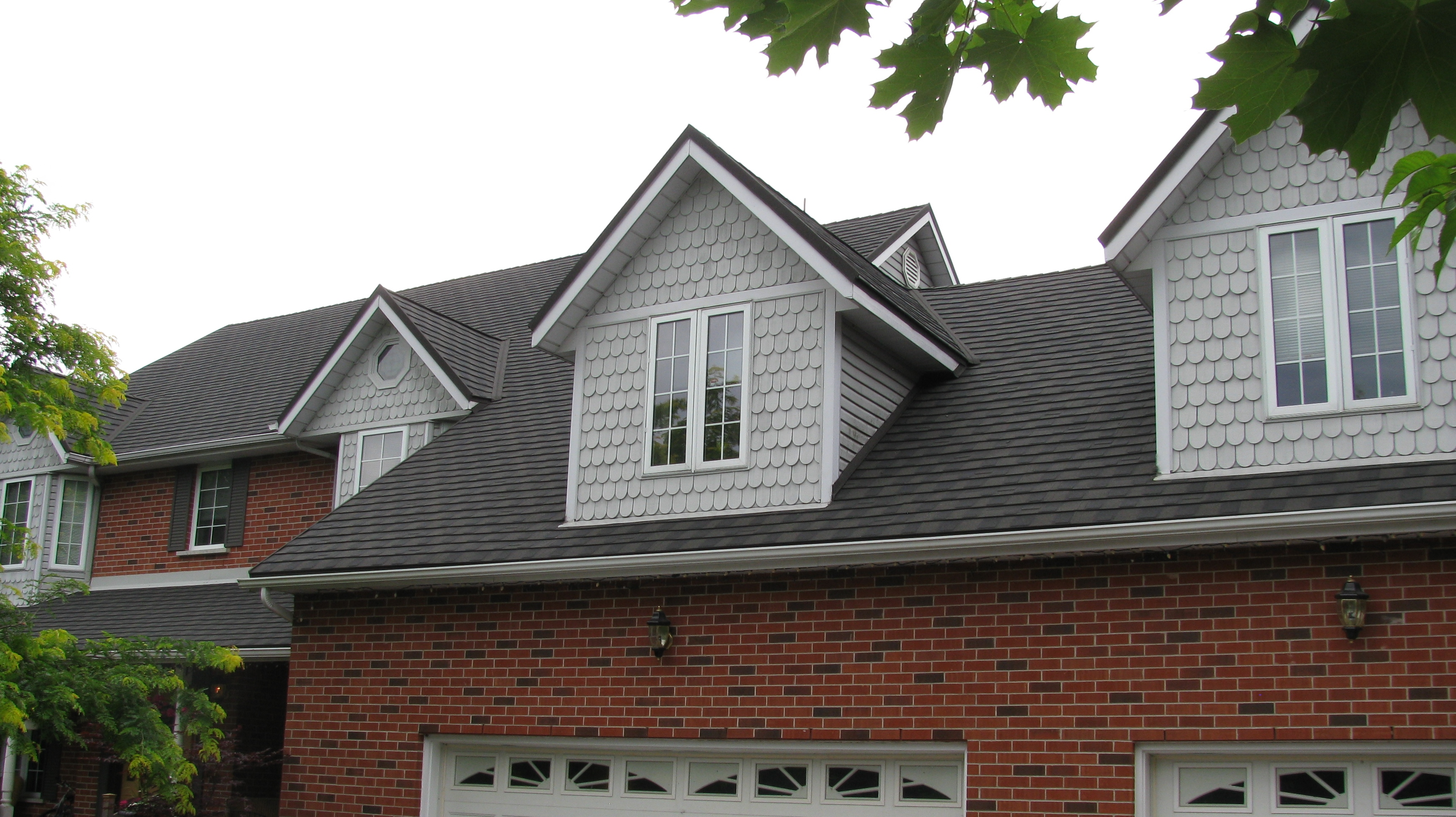 The Cool Grey Scalloped Siding Of This House Is Offset By Steel Granite  Ridge Shingle In