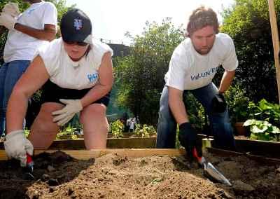RA Dickey and Volunteer Planting Flowers