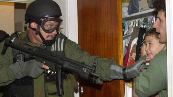 In this April 22, 2000 file photo, Elian Gonzalez is held in a closet by Donato Dalrymple, one of the two men who rescued the boy from the ocean, right, as government officials search the home of Lazaro Gonzalez for the young boy in Miami. U.S.-based relatives fought to keep Gonzalez, rescued at sea at age 5 after his mother died, but U.S. officials finally sent him back to his father in Cuba. On Wednesday, Dec. 17, 2014, the U.S. and Cuba agreed to re-establish diplomatic relations and open economic and travel ties, marking a historic shift in U.S. policy toward the communist island after a half-century of enmity dating back to the Cold War.