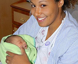 Young mom holding newborn in hospital room.