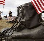 Boot with US flag in it rests on ground in memorial gravesite at anti-war protest near President Bush's ranch in Crawford