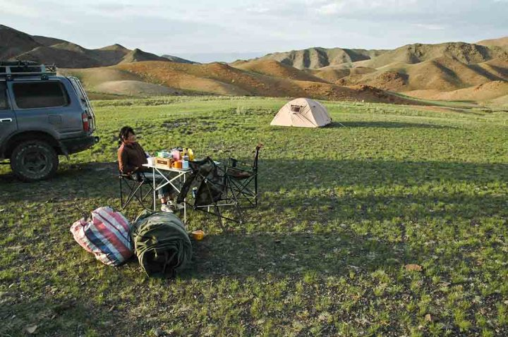 Our camp site for the first night on this trip to the Mongolian Gobi Altai. My cook sits at our dinner table. The dry creek bed is off to the right, my swag is in the foreground, and the only vegetation in sight is a very low green herb.