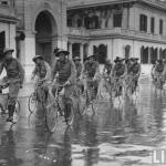 A troop of men bicycling in Rome through the rain.