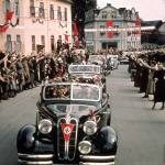 Nazi staff cars entering a Sudetenland village to receive an enthusiastic reception