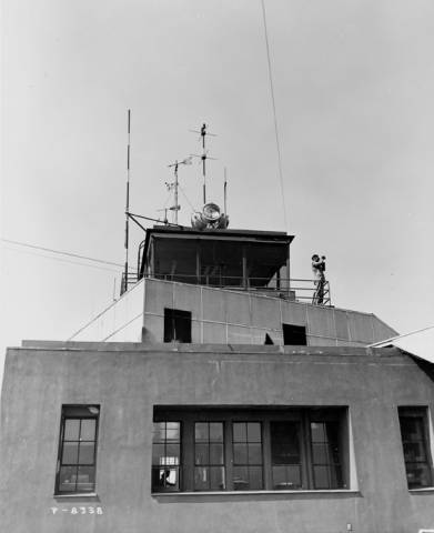 "Lockheed Air Terminal Control Tower, exterior view, looking up from the ground. Man standing on deck, looking through binoculars. What appears to be a second story is a fake building, built as a part of the camouflage for the airport. Numbered ""894."" 8 x 10 in. black and white photograph."