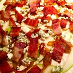 Layer on sliced pear, caramelized onion, crumbled blue cheese and bacon pieces