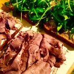 Spread horseradish cream cheese on one slice and top with roast beef, then butter the other slice and top with arugula