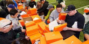 People hunting for their favorite pairs at a surplus shoe sale at the University of Oregon - Home of the Mighty Ducks