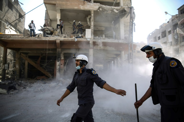 Des Casques blancs une organisation de secouristes en zone rebelle recherchent des survivants après des frappes aériennes sur la ville de Douma le 5 octobre 2016 en Syrie