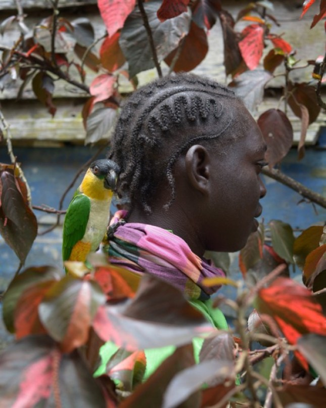 Photo: Banai Meklien, from Kourou in French Guiana, with a parrot, participant in Gaama's funeral in Asindoopo, Suriname. © Nicola Lo Calzo/L'agence à paris.