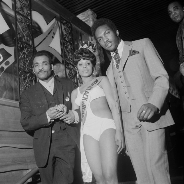 "Photo: (unidentifed) Miss Black & Beautiful escorted by two men, Hammersmith Palais, London, 1970s. From the portfolio ""Black Beauty Pageants"". Courtesy of © Raphael Albert/Autograph ABP."