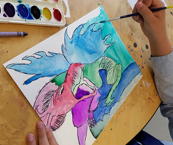 Student paints a dragon based on dragons from various worldwide cultures in Art History.