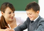 Close-up of teacher assisting student with lesson (10-11)