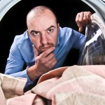 Why a dirty dryer vent is a safety hazard in your home man looking in dryer