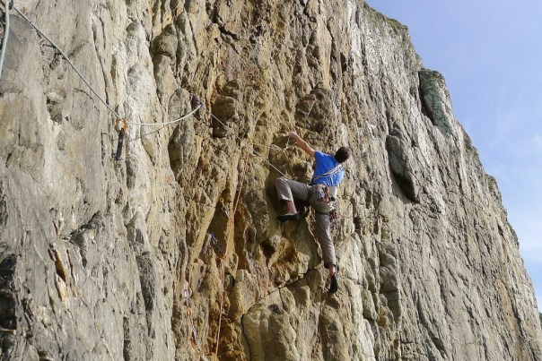 Big Tim Neil finding the line of least resistance on Main Cliff on the first ascent of 'Main Wall' E1 5b. Photo - Calum Muskett