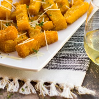 Feature image of polenta on a platter next to a glass of chardonnay