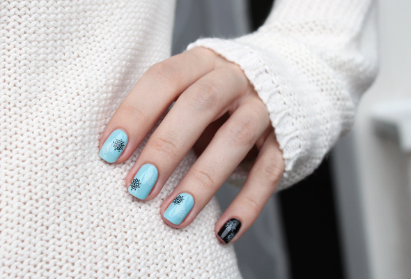 Black snowflakes nail design over blue