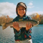 Charles Diphno, 8, of Naugatuck, poses with a 6-pound trout he caught at Lake Quassapagh recently.