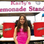 Karly Laliberte poses in front of her lemonade stand May 21.