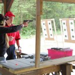 High Rock Shooting Association instructor Dave Mastrianna helps Nicole Braman of Wolcott, a first-time shooter, during the association's second annual Women on Target shooting clinic last weekend. KEN MORSE