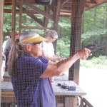 Joyce Pallman aims at the target and prepares to shoot during the Women on Target shooting clinic this past weekend at the High Rock Shooting Range in the Naugatuck State Forest as High Rock Shooting Association instructor Hank Mazako stands behind her. –KEN MORSE