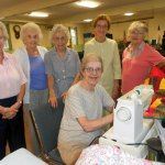 Local quilters, standing from left, Kathryn Green, Eleanor Lawson, Mildred Evensen, Micky Shea, and Erica Roland. At the machine is Dotty Obar. –CONTRIBUTED