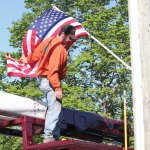David Plante, a worker from Ed The Treeman, unravels an American flag he installed on a utility pole along Route 68 in Prospect in May. The flag was one of 103 installed along the streets of downtown purchased through donations to the Prospect Flag Fund. The fund is planning a special donor recognition display for Town Hall. –FILE PHOTO