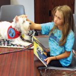 Emily Orzechowski, 9, of Prospect, pets Flower Girl, a therapy dog, during a reading therapy session Oct. 6 at the Prospect Library. The library is running a Reading Therapy Dog program through mid-December. –LUKE MARSHALL
