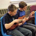 Community School fifth-graders Robert Hansen, left, and Jackson Barter play 'Jingle Bells' on the ukulele during class in December. The ukuleles were purchased through Region 16's innovative grant initiative. –ELIO GUGLIOTTI