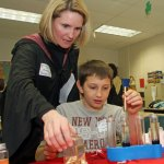 Brandon McCusker gets a hand by presenter Deb Flaherty, a history teacher at Woodland Regional High School in Beacon Falls, as he mixes elixirs in the 'Potions Class with Professor Bubbly Brew' during last year's Minds in Motion program at Long River Middle School in Prospect. This year's program will be held March 16 at the school. –RA ARCHIVE