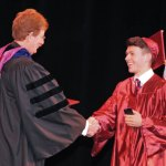 Naugatuck High School graduate Justin Rinaldi shakes hands with Superintendent of Schools John Tindall-Gibson before accepting his diploma Monday night at the Palace Theater in Waterbury. -LUKE MARSHALL