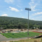 Constructions workers lay down the new artificial turf field at Naugatuck High School. –KYLE BRENNAN