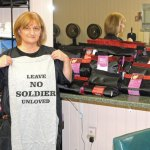 Dolly Lengyel, owner of Personal Pampering in Naugatuck, holds one of the T-shirts she's selling at her salon Nov. 18. The money from the sale of the T-shirts will be used to send items to troops serving overseas. LUKE MARSHALL