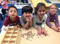 Naugatuck Day Care raised $245.39 for the Naugatuck Ecumenical Food Bank during a coin drive in April. The children, including from left, Anthony, Romulo, Luiza and Emma helped to sort out the coins. –CONTRIBUTED