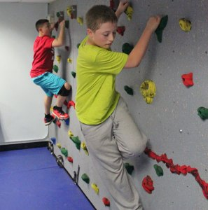 Naugatuck residents Derrick Jagello, 12, in front, and Tyler Demoura, 11, make their way across the traverse climbing wall in the newly redesigned youth room at the Naugatuck YMCA May 15. The YMCA has launched a new afterschool program, #Go2y, for middle school students. –ELIO GUGLIOTTI