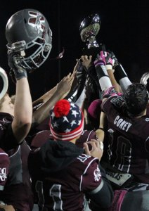 Naugatuck players hold up the George Pinho Memorial Trophy in celebration last year after the Greyhounds beat Woodland. The two squads will face off Friday night for the right to take home the trophy. –FILE PHOTO