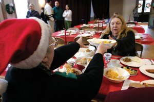 Dolly F.H. Stevenson of Athen's, Vt., left, and Janice Konna of Naugatuck, right, trade dishes during the annual Joy of Christmas Dinner at St. Michael's Church in Naugatuck in 2005. This year's dinner is Christmas Day, Dec. 25, from 12 to 2 p.m. –RA ARCHIVE