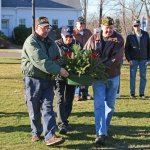 Veterans and Prospect residents, from left, Rich Chabot, Jim Borbas and Tom Czarkosky place a wreath at the foot of the Civil War monument on the Prospect Town Green Dec. 7 during a ceremony to honor those who died on Dec. 7, 1941 during the attack on Pearl Harbor. –LUKE MARSHALL