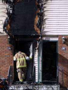 A firefighter surveys a room inside the scene of a fire at Meadowland Estates in Naugatuck on Saturday. Multiple condos were destroyed by fire and others were heavily damaged by smoke at the complex, which is off Horton Hill Road. –REPUBLICAN-AMERICAN