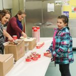 Western Elementary School third grader Emma Jackson, right, takes an ice cream as computer teacher Lindsay Swiatek, left, and physical education teacher Lauren Warren scoop out servings Feb. 4 at the school during an ice cream social to raise money for second-grader Olivia Thompson, who had underwent heart transplant surgery in November. The ice cream social drew over 200 people and raised more than $400 for Thompson and her family, Western Principal Brenda Goodrich said. –LUKE MARSHALL