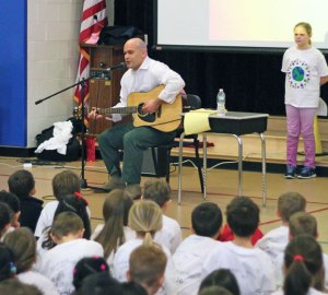 President of CARE Campaign Mike Finoia performs a song Tuesday during an assembly at Prospect Elementary School to kick off a new kindness campaign in Region 16. –ELIO GUGLIOTTI