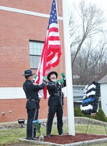 Naugatuck police Sgt. Derek Vostinak, left, and Det. Kevin Zainc raise an American flag March 17 in front of the Naugatuck Police Department during a ceremony to mark the 25th anniversary of the death of Officer Nancy Nichols, who was killed in the line of duty. –ELIO GUGLIOTTI